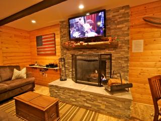 Wood burring fireplace with ledger stacked stone and flat screen TV