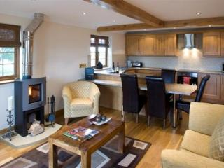 Cosy lounge area in one of the cottages with log burning fire and fully equipped kitchen