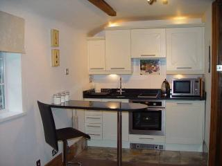 The Den -Fully equipped kitchen with granite breakfast bar and stools