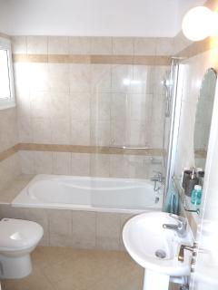 Bathroom with natural light. Bath/shower with shower screen