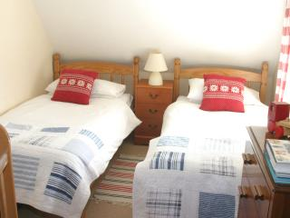 Second bedroom with twin beds and wooden cot