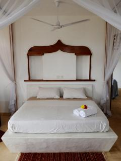 Large Comfortable beds with Mosquito nets from the Ceiling and Fan inside the mosquito net