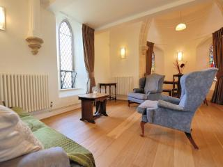 Open plan living space, with wooden floors and stone arched windows