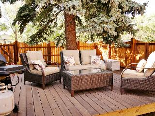 WIcker seating set in front of huge Blue Spruce