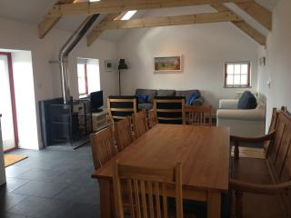 Spacious dining and cosy living space with wood burner and doors out to the terrace.