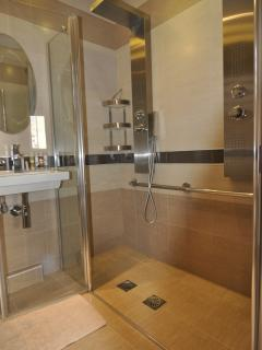 En suite bathroom with wheelchair accessible double roll in shower