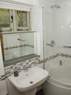 The ensuite bathroom has a curved bath with power shower over