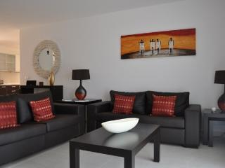 Living/dining area with luxury furnishings. Two large leather sofas, one of which converts to a bed.