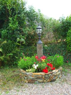 Flower bed and lamp in front of cottage