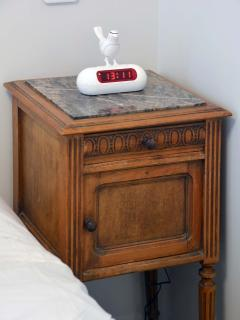 The antique night-stand and alarm clock.