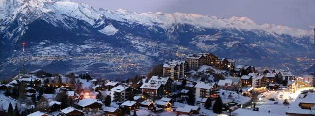 Actual view from the lounge area balcony of Nendaz overlooking towns in the Rhone Valley at dusk