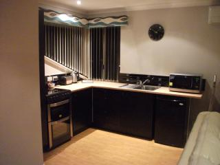 Upstairs kitchen with cooker, microwave and fridge.