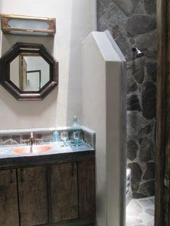 Bath has stone shower, five skylights and a copper sink