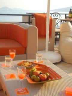 Sizzling orange colours accessorize the cream outdoor furniture.