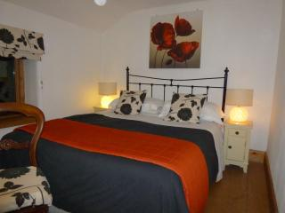 King size main bedroom in the evening with cosy underfloor central heating on solid oak floors
