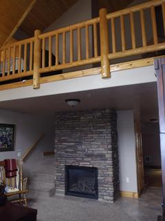 View looking up from cozy family room to the loft