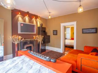 The spacious master bedroom features a cozy seating area, decorative fireplace, and flatscreen TV