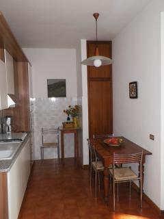 Kitchen next to dining area and sitting room and with large doors leading onto veranda and gardens.