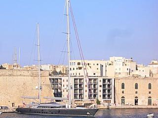 A two-mast super-yacht moored behind St Angelo Mansions
