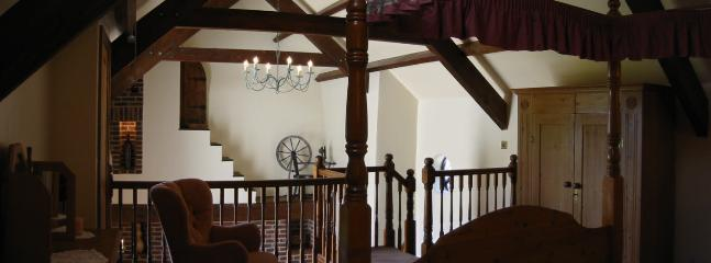 A romantic cottage with stairs to minstrel-style gallery bedroom with a four-poster bed