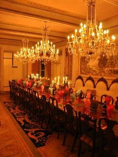 The great dining hall seats 40-50 persons, intimately lit by the crystal chandeliers