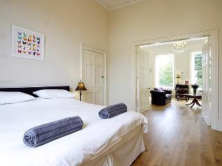 Regency bedroom with wedding doors leading to the elegant open plan living room.