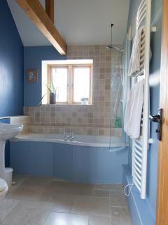 The family bathroom comprises a WC, basin and bath with a shower over