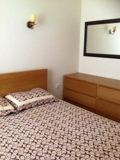 Main bedroom with large wardrobe, chest of drawers, double bed and air conditioning