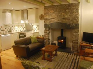 Cosy living area with wood floors, beams, stone inglenook and woodburner