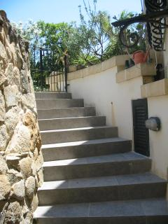 Stairs leading down from front garden area to apartment