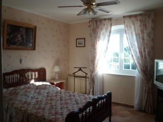 chambre beige avec lit double , télévision et climatisation , pour votre confort