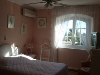 chambre  rose  avec lit double , climatisation  et télévision