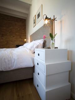 Large bedroom with kingsize bed and oak flooring.