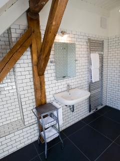 Bathroom furnished with quality fittings and incorporating the original building beams.
