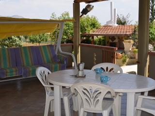veranda coperta con tavolo sedie e dondolo