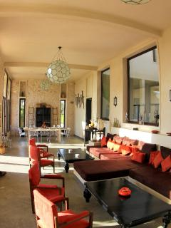 A huge living room with a fire place and large windows opening a view to the garden