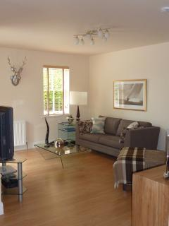 Open plan living area with comfy sofa and chaise longue..
