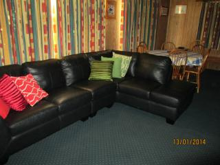 The comfortable living area has a leather lounge, TV and DVD player and the dining table.