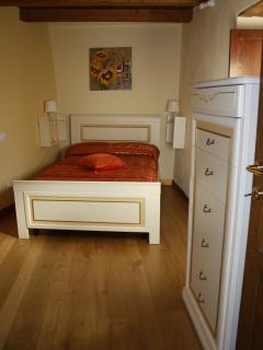 Camera da letto  con pavimento in legno di quercia e mobili di classe con bordure in oro