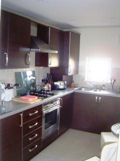 Separate, fully-equipped modern kitchen with integrated appliances, washer/dryer, microwave