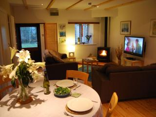 The spacious open plan lounge, complete with wood burning stove + 42' TV, is cosy + inviting.