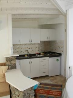 The kitchenette is complete with all amenities and is equipped with a large fridge, hob and sink.