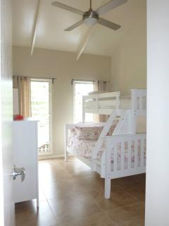 2nd bedroom with double bed and single bed, tallboy, built in storage, louvre windows & ceiling