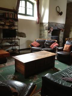 Comfy seating area with wood burner. The sitting room has a number of sofas and easy chairs, TV,
