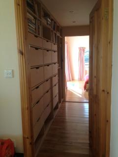 Corridoor to master bedroom lined with bookshelves and empty drawers for unpacking