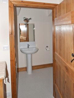 Sparkling new, bright and light en-suite with mirror, glass shelving and feature oak door,