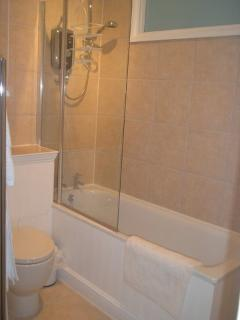 The tiled Bathroom with Bath and Shower.The Hand Basin is to the right. Sorry about the poor photo.