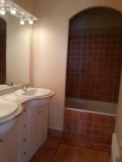 La salle de bain est dotée d'une double vasque et d'une baignoire.