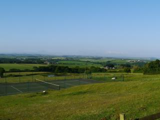 Spectacular views over the tennis court across the fields down to the coast.