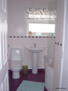 Bathroom with P shaped bath shower over bath